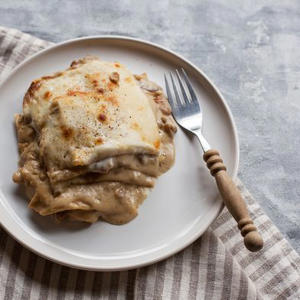 a piece of food on a plate: Vincisgrassi (Wild Mushroom and Prosciutto Lasagna)