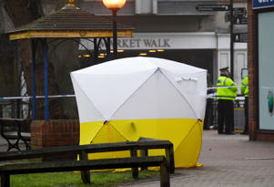 Police officers stand at crime scene tape, as a tent covers a park bench on which former Russian inteligence officer Sergei Skripal, and a woman were found unconscious after they had been exposed to an unknown substance, in Salisbury, Britain, March 6, 2018.