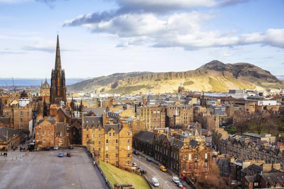 Slide 1 of 21: Looking over the buildings and roofs of Edinburgh Old Town to the cliffs of Salisbury Crags and the peak of Arthur's Seat.