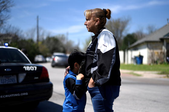 Isaac Machado hides behind his hat against his mother Delores just outside the scene of an explosion on Galindo Street in Austin, Texas, U.S., March 12, 2018.