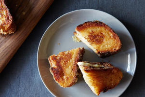 a plate of food with a slice cut out: Gabrielle Hamilton's Grilled Cheese Sandwiches