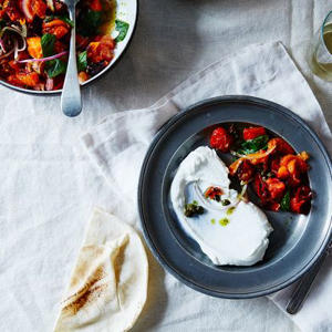 a bowl of food on a table: Half Roasted Tomato Salad with Salsa Verde