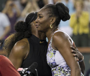 Venus Williams, right, hugs opponent and sister Serena Williams after defeating her in the third round of the BNP Paribas Open tennis tournament at the Indian Wells.