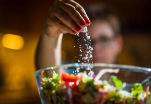 Woman adds salt to salad
