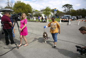Local resident Adrienne Rubel walks her dog Barney through a media staging area near the home where Austin serial bomber Mark Anthony Conditt lived in Pflugerville, Texas, U.S., March 22.