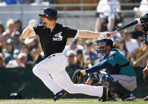 Chicago White Sox's Adam Engel follows through on a swing during the fourth inning of a spring training baseball game against the Seattle Mariners Friday, March 23, 2018, in Glendale, Ariz.