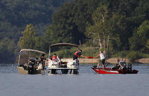 A civilian in a boat hands Missouri State Police officers a life vest the state police search the waters of Table Rock Lake on Friday, July 20, 2018 in Stone County, Mo. On Thursday evening strong winds whipped up waves in the water that caused a Duck Boat with 31 tourists to sink, killing 17 people and injuring seven others