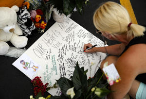 A woman writes a message during a candlelight vigil in the parking lot of Ride the Ducks Friday, July 20, 2018 in Branson, Mo. One of the company's duck boats capsized Thursday night resulting in over a dozen deaths on Table Rock Lake. (AP Photo/Charlie Riedel)