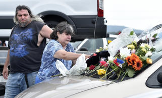 Flowers left on the vehicle of William and Janice Bright as a memorial were gathered by William Bright's sister Karen Abbot of Mountain View, Mo. on Friday, July 20, 2018, in Branson, Mo. Her son, William Krebs, offered a comforting touch. The Brights were two of 17 people who died when the amphibious vehicle they were riding in on Table Rock Lake capsized due to high winds on Thursday. The Bright's vehicle was still in the parking lot of the Ride the Ducks attraction, where they had boarded for the ride the day before.