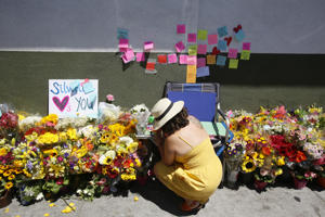 A makeshift memorial of flowers, candles and notes grows on the sidewalk outside the Los Feliz Trader Joe's store in Los Angeles, Sunday, July 22, 2018. A day earlier, Trader Joe's employee Melyda Corado was shot and killed at the store by a suspect being chased by police. (AP Photo/Damian Dovarganes)
