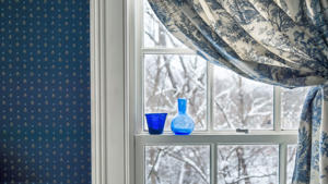 Two blue bottles decorating a window with curtain, winter scene on background. Copy Space.