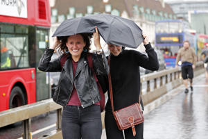 Pedestrians shelter from the rain beneath umbrellas as rain falls in central London