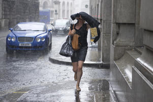 A member of the public runs as heavy rain falls