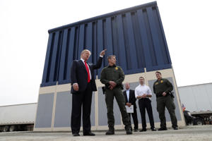 President Donald Trump talks with a U.S. Customs and Border Protection (CBP) Border Patrol Agent while participating in a tour of U.S.-Mexico border wall prototypes near the Otay Mesa Port of Entry in San Diego, Calif. on March 13, 2018.