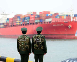 Soldiers wait for a container ship to berth at Qingdao Port on March 8, 2018,in Qingdao, China.
