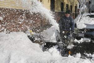 Al Gambale clears snow on Cottage Street in Boston, Wednesday, March 14, 2018. The Boston area was hit with it's third nor'easter of the month on Tuesday, a storm that brought powerful gusts of wind and over a foot of snow.