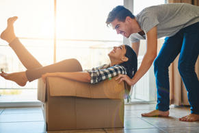 Man pushing his girlfriend around in a box while they move into their new home together