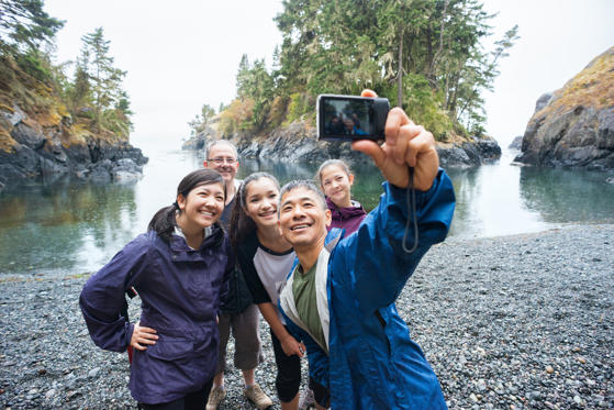 Slide 1 of 21: A real extended family of multi-ethnic and multi-generational backpackers in the wilderness pose of a selfie on a deserted beach surrounded by islands and forest with the ocean in the background.  Rainy day in a wilderness park.  Whiffen Spit, Sooke, British Columbia, Canada.