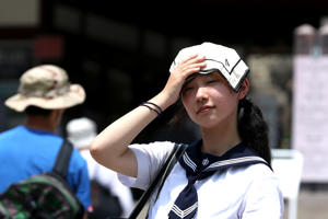 A Japanese high school student uses a handkerchief to cover her head from sunlight as city temperature reach 36 degree celsius on July 25, 2018 in Himeji, Japan.