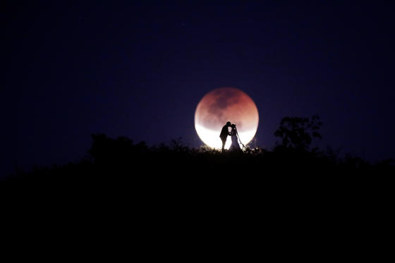 Slide 1 de 43: A couple poses for photo during a total lunar eclipse from in Brasilia, Brazil, July 27, 2018. REUTERS/Ueslei Marcelino