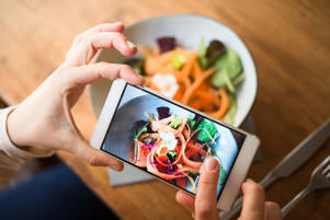 A woman photographing a plate of salad on her smartphone