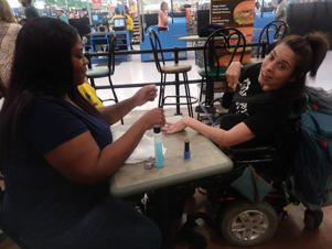 Walmart employee Ebony Harris painted a customer's nails during her break after hearing the woman was turned away from a nail salon because of her disability.