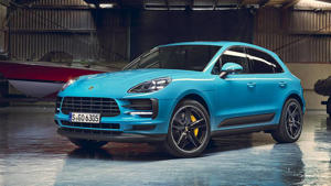 a blue car parked in front of a building: Porsche Macan 2019
