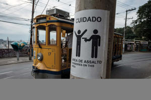 Rio de Janeiro's famous street car passes by a sign warning against robberies on an electricity pole in the Santa Teresa district, where local residents recently protested against the high levels of violence, in Rio de Janeiro, Brazil, on June 5, 2017. According to the Atlas of Violence 2017 published by the Brazilian Institute of Applied Economic Research (IPEA) and the Brazilian Public Security Forum today, this country of 200 million people recorded 59,080 homicides in 2015, or 161 per day. / AFP PHOTO / YASUYOSHI CHIBA        (Photo credit should read YASUYOSHI CHIBA/AFP/Getty Images)