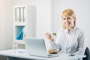 Woman eating salad at office