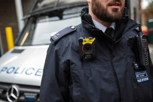 A body-worn camera (BWC) is pictured on the uniform