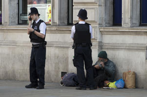 Police officers talk to a homeless man in central London.   (Photo by Laura Lean/PA Images via Getty Images)