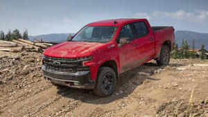 a red car parked on a dirt road: 2019 Chevrolet Silverado: First Drive