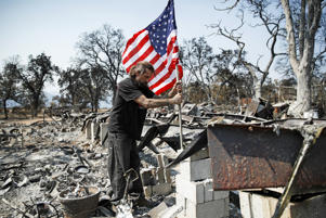 Freddie Cox plants a flag at the charred remnants of his godfather, Ed Bledsoe's home, on Aug. 12, in Redding, Calif. Bledsoe's wife, Melody, great-grandson James Roberts and great-granddaughter Emily Roberts were killed at the home in the Carr Fire.