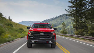 a red car going down the road: 2019 Chevrolet Silverado: First Drive
