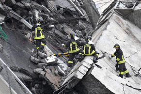Rescuers at work amid the rubble after a highway bridge collapsed in Genoa, Italy, 14 August 2018.