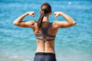 Sportswoman showing her back muscles on background of sea.