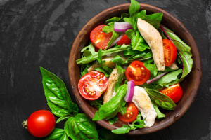 Fresh salad with chicken breast, arugula, basil and tomato.