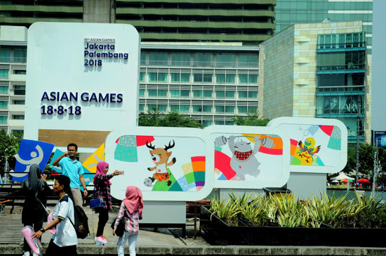 Slide 1 of 11: CAPTION: Jakarta residents take pictures in front of the screen countdown the implementation of Asian games installed in the park roundabout monument welcome to Jakarta, Indonesia On September 17, 2017. The Asian Games will be held from 18 August to 2 September 2018 in Palembang and Jakarta. (Photo by Dasril Roszandi/NurPhoto via Getty Images)