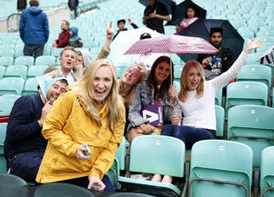 General view of fans under umbrella as rain stop play during Surrey against Essex
