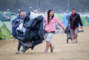 EAST LULWORTH, DORSET - JULY 29: Festival goers carry their broken tent blown over in the wind as they walk in the wind and rain at Camp Bestival, at Lulworth Castle near East Lulworth on July 29, 2018 in Dorset, England. The Met Office has issued a yellow warning for wind and rain for some parts of the UK today giving a brief respite from the heatwave conditions. The child orientated and family friendly festival, which finishes today, is the sister festival for Bestival, which is hosted at the same site and opens next weekend. (Photo by Matt Cardy/Getty Images)