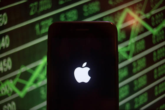 圖片 1 /共 41 張: BANGKOK, THAILAND - 2018/07/30: An iPhone displays the Apple logo with a background of a market value increasing on the stock exchange behind. (Photo by Guillaume Payen/SOPA Images/LightRocket via Getty Images)