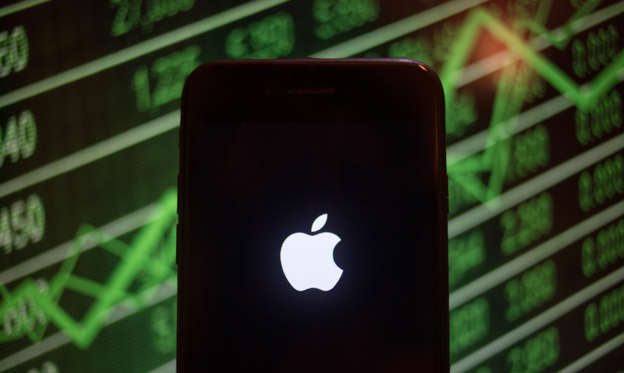 Slide 1 of 46: BANGKOK, THAILAND - 2018/07/30: An iPhone displays the Apple logo with a background of a market value increasing on the stock exchange behind. (Photo by Guillaume Payen/SOPA Images/LightRocket via Getty Images)