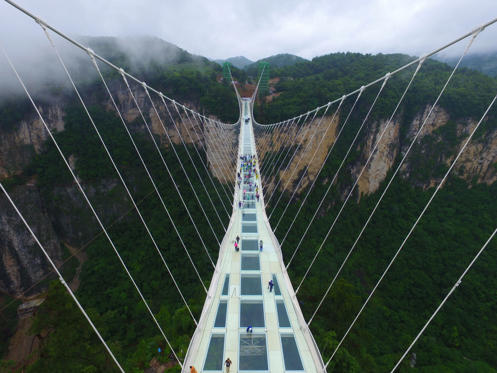 Slide 2 of 19: Aerial view of the glass-bottomed bridge receiving a safety test at Zhangjiajie Grand Canyon on June 25, 2016 in Zhangjiajie, Hunan Province of China. World's tallest and longest glass-bottomed bridge has been completed and took a global broadcast through television and internet medias to show its safety. More than thirty citizens and visitors struck the bridge with hammer in the test event. (Photo by VCG/VCG via Getty Images)