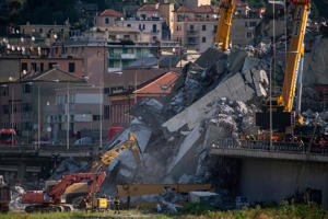 Rescuers work among the rubble and wreckage of the Morandi motorway bridge in Genoa on August 17, 2018, three days after a section collapsed. - Rescue workers in Genoa have toiled for a third night in the wreckage of a collapsed bridge, continuing the desperate search for people still missing after the accident, which left at least 38 people dead. Italy's populist government intensified its attacks on the viaduct operator amid rising anger over the tragedy and the structural problems that have dogged the decades-old Morandi bridge, which buckled without warning on August 14, sending about 35 cars and several trucks, along with huge chunks of concrete, plunging 45 metres (150 feet) onto railway tracks below. (Photo by MARCO BERTORELLO / AFP)        (Photo credit should read MARCO BERTORELLO/AFP/Getty Images)