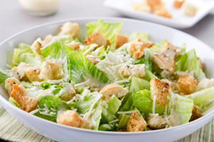 SEVERAL MORE IN THIS SERIES. Closeup of a fresh caesar salad, with romaine lettuce hearts, croutons, parmesan cheese and dressing.  Dressing and croutons in background.  Very shallow DOF.