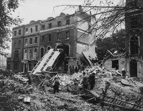 Slide 1 of 50: A bus is left leaning against the side of a terrace in Harrington Square, Mornington Crescent, in the aftermath of a German bombing raid on London in the first days of the Blitz, 9th September 1940. The bus was empty at the time, but eleven people were killed in the houses.