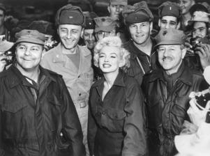 19th February 1954: American actor Marilyn Monroe (1926 - 1962) smiles while posing with soldiers while entertaining U.S. troops stationed in Korea. Monroe wears a military uniform.