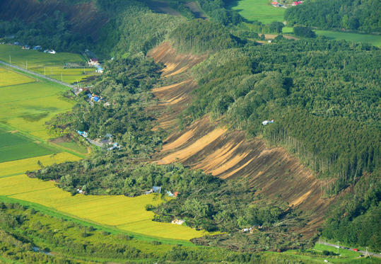 圖片 1 /共 26 張: This picture shows an aerial view of houses damaged by a landslide in Atsuma town, Hokkaido prefecture on September 6, 2018, after an earthquake hit the northern Japanese island of Hokkaido. - A powerful 6.6 magnitude quake hit the northern Japanese island of Hokkaido on September 6, triggering landslides, bringing down several houses, and killing at least one person with several dozen missing. (Photo by JIJI PRESS / JIJI PRESS / AFP) / Japan OUT        (Photo credit should read JIJI PRESS/AFP/Getty Images)