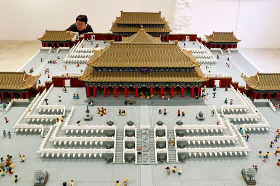Slide 1 of 22: A woman takes a photo of the Forbidden City model made of Lego bricks on display at the Royal Modern Household Exhibition after opened by Danish Crown Prince Frederik at the Danish Cultural Center in 798 art district in Beijing, Saturday, Sept. 23, 2017. (AP Photo/Andy Wong)
