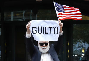"Protester Bill Christeson holds up a sign saying ""guilty"" as the first count of guilty comes in at he trial of former Donald Trump campaign chairman Paul Manafort, at federal court in Alexandria, Va., Tuesday, Aug. 21, 2018. (AP Photo/Jacquelyn Martin)"